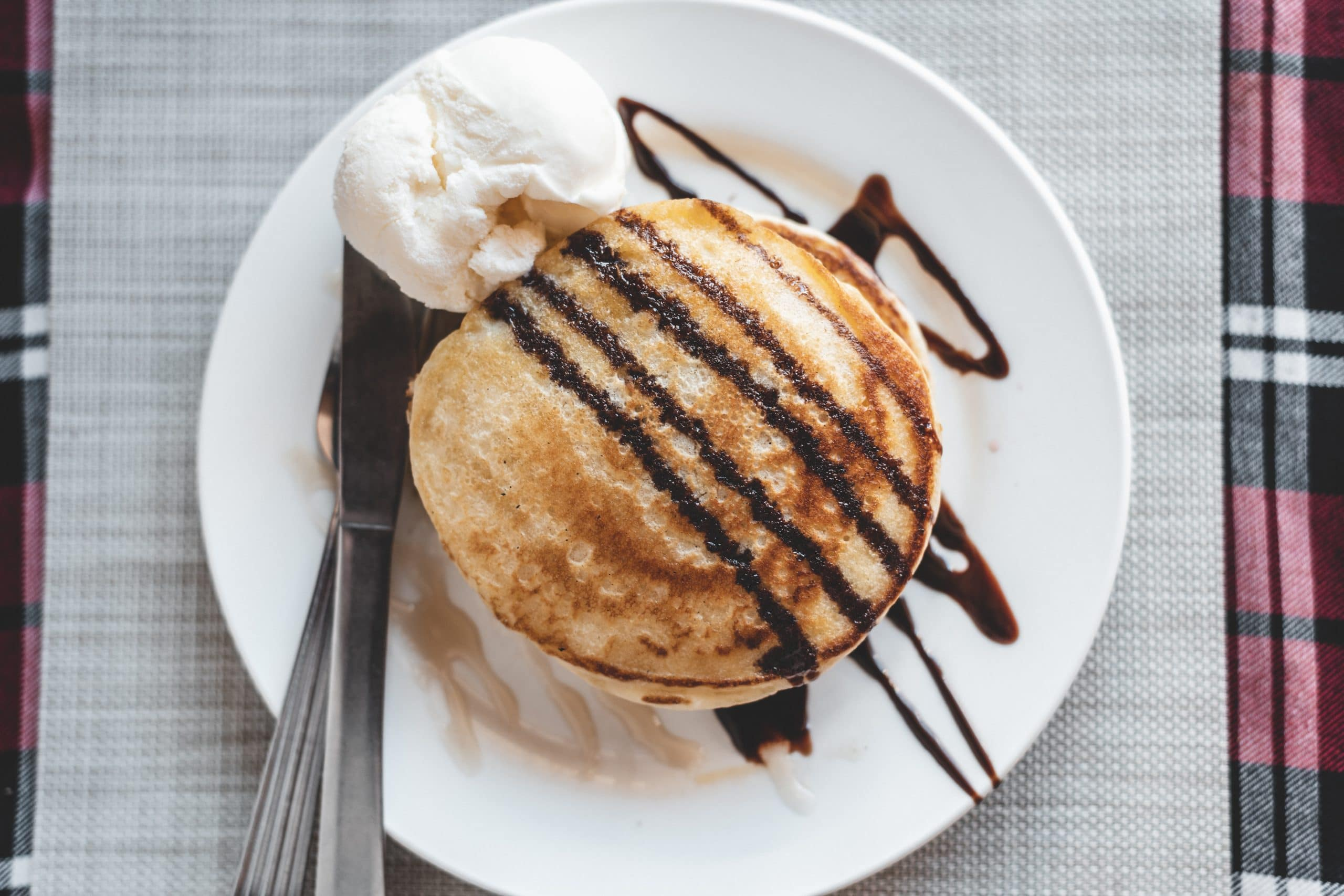 Pancakes topped with honey and chocolate with vanilla ice cream.
