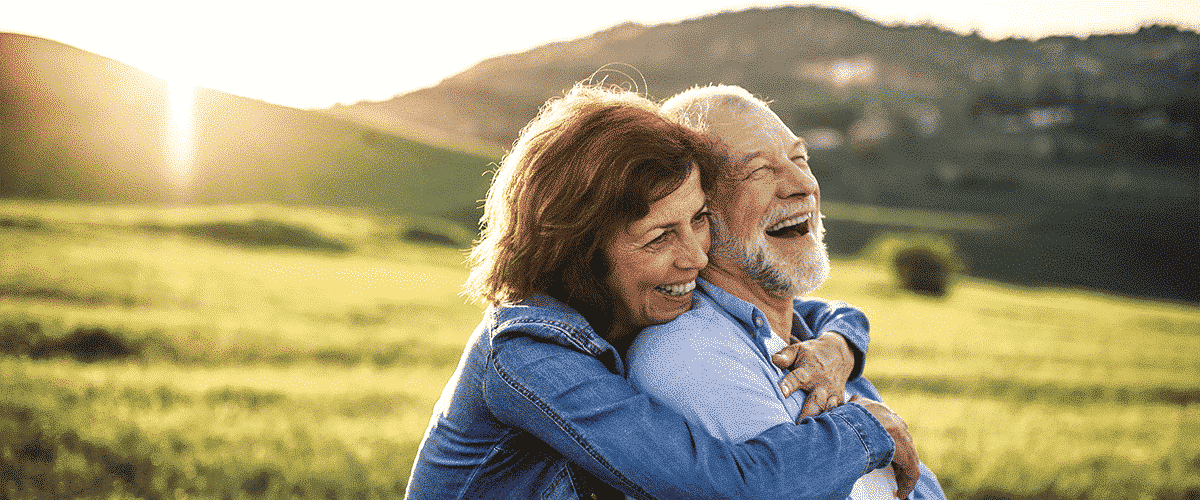Two people hugging and smiling in a field with the sun behind them. Image ilustrates lack of Vitamin D Deficiency