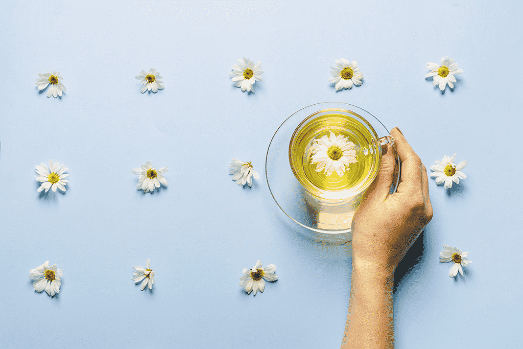 A mug of flowered chamomile tea in a woman's hand on a blue background with flowers spread out. Floral summer background. Contains flavonoids