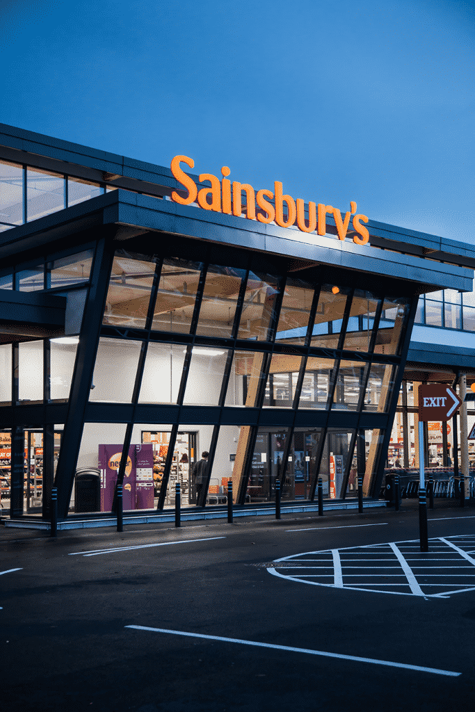 Weymouth Sainsbury's Store after sunset taken from the car park, people can be seen inside the shop. The Sainsbury's sign is illuminated