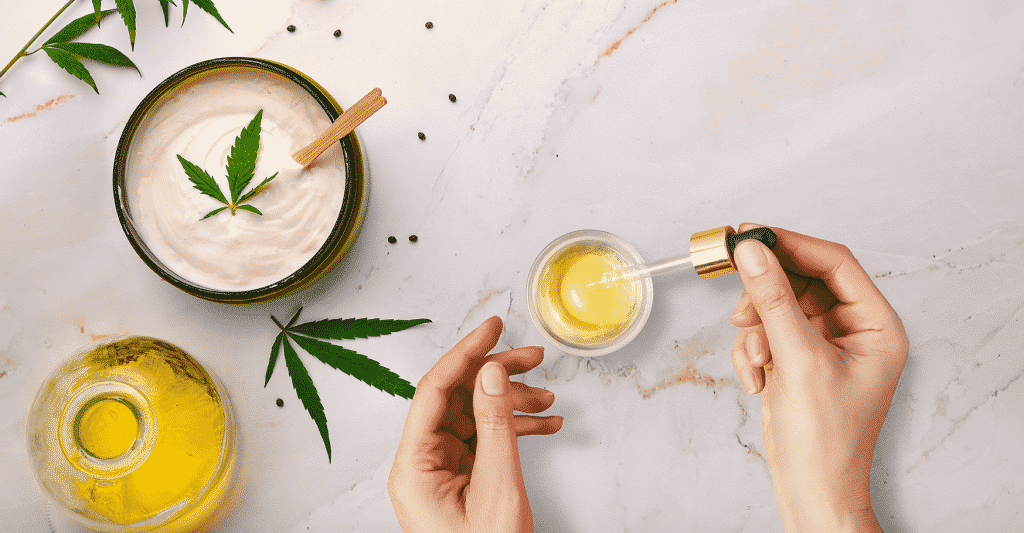 Cannabis leaf in cream with hands holding pipette of oil containing cannabinoid
