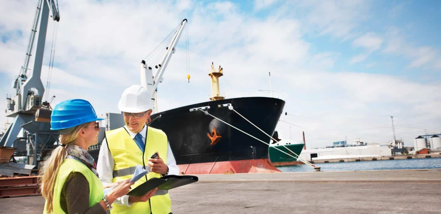 Two dock workers holding paperwork while standing in the shipyard