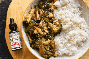 Cashew and broccoli vegan stir fry next to a bottle of dragonfly cbd