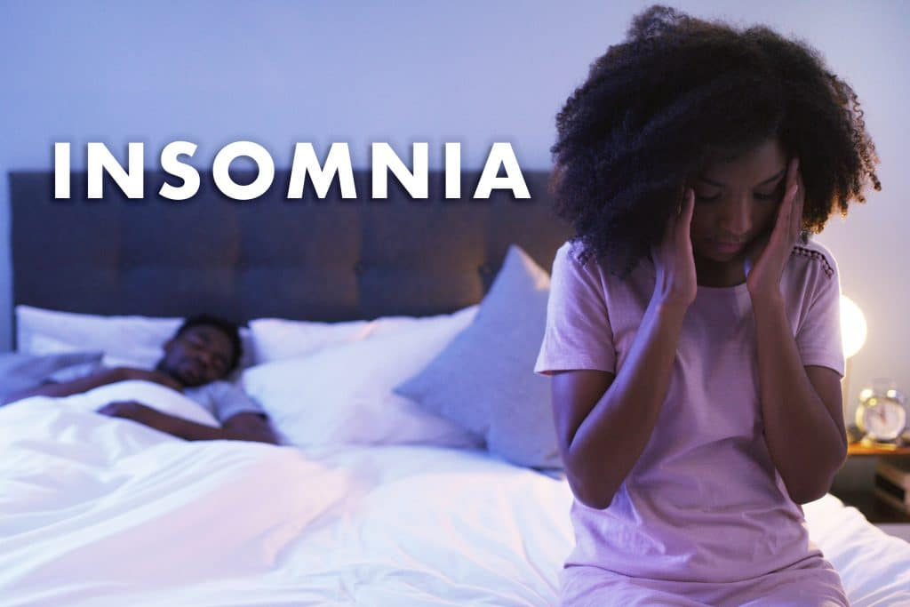 Shot of a concerned looking young woman suffering with insomnia sitting on a bed with her husband sleeping in the background