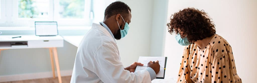 Close up of a doctor doing a medical exam while both him and the patient are wearing protective masks