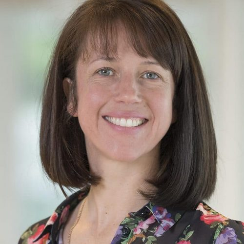Thumbnail image of Expert Prof. Saoirse O'Sullivan leaning on a railing, smiling at camera.