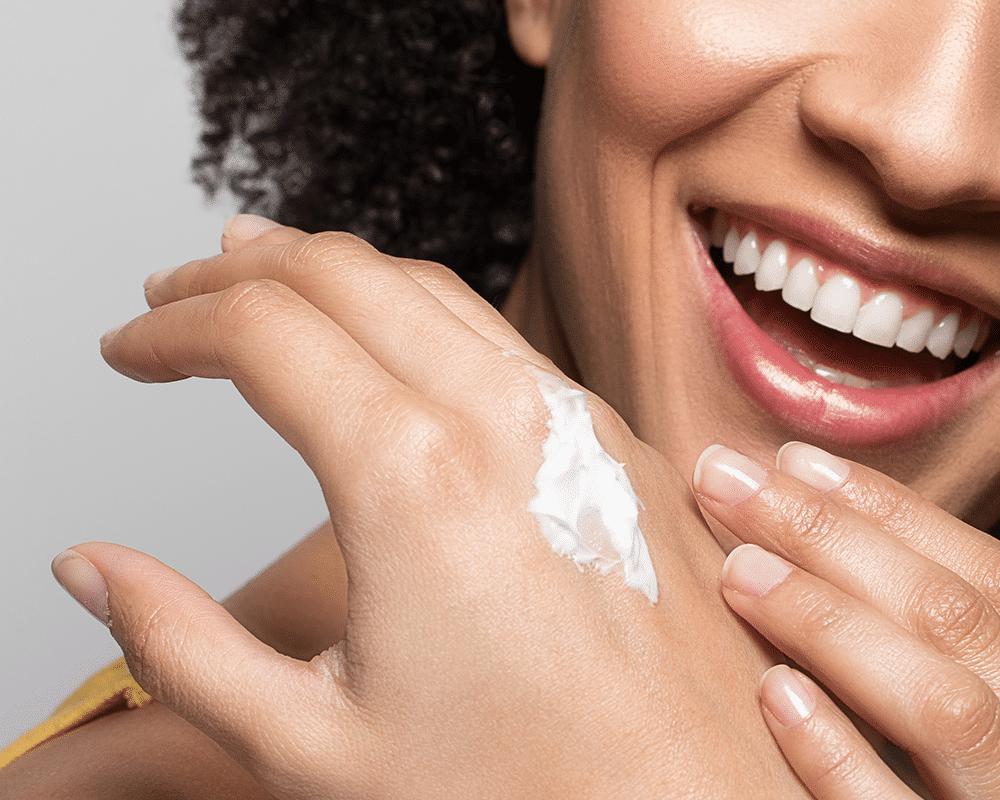 Woman smiling, applying CBD skincare onto hand